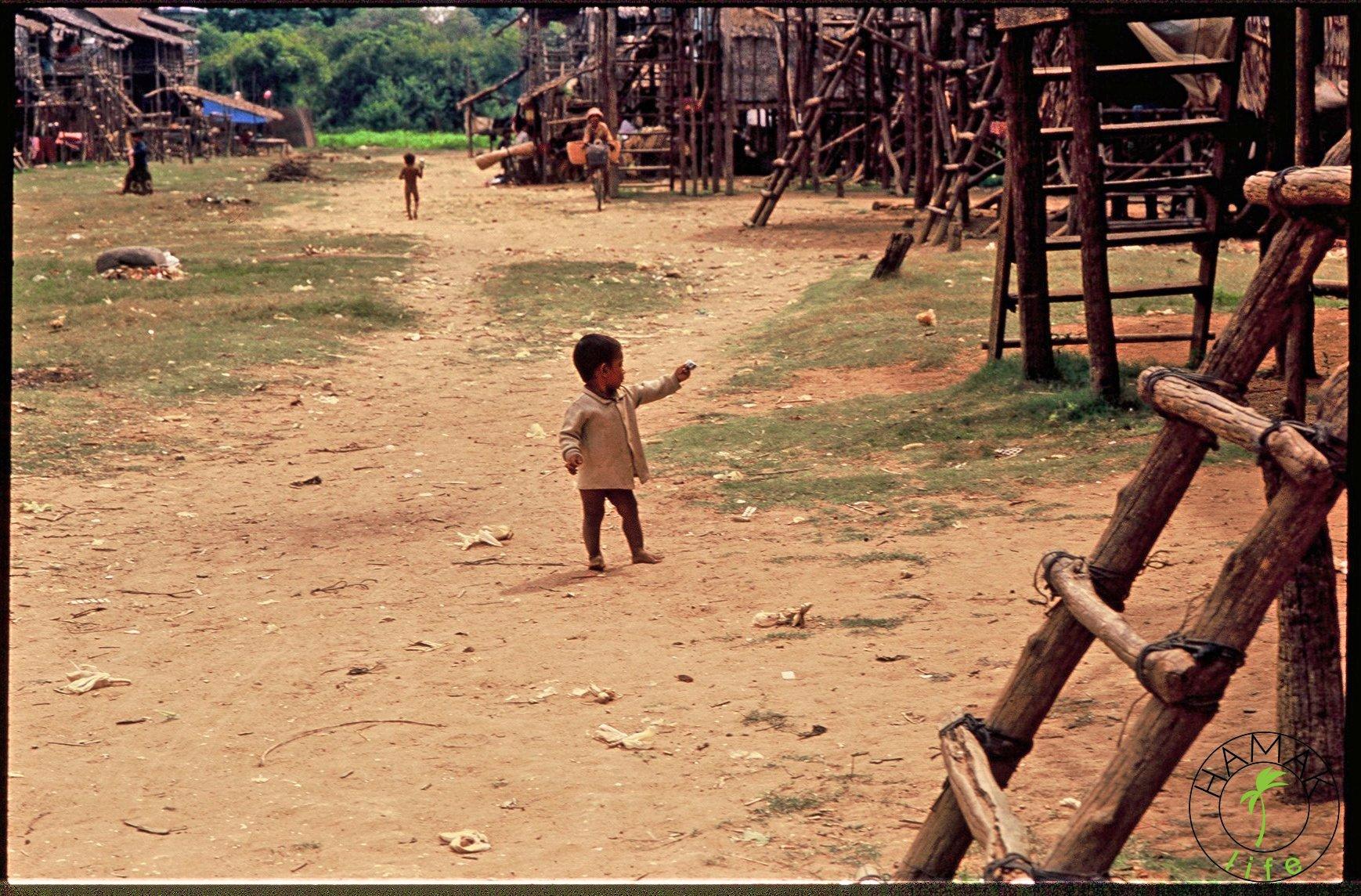 Chłopiec w wiosce na palach w Kambodży