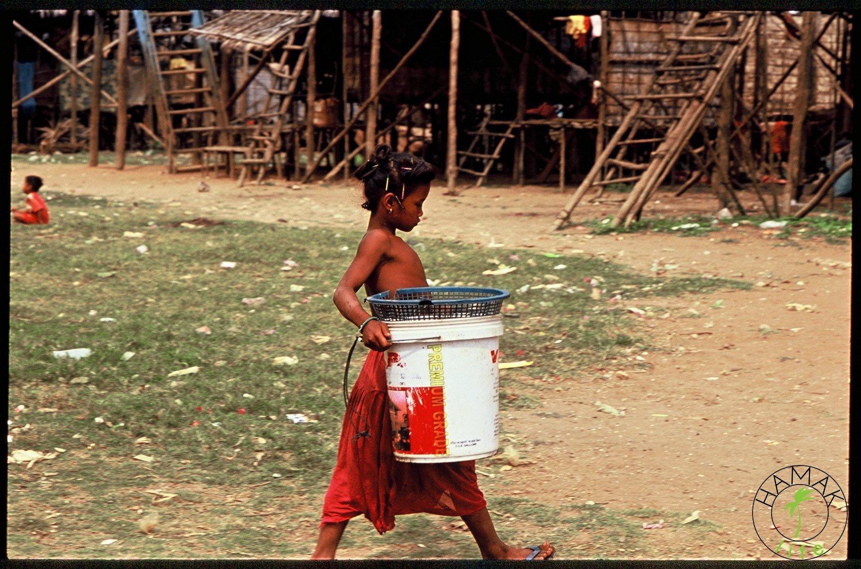Dziewcznyka z koszem w wiosce w Kambodży