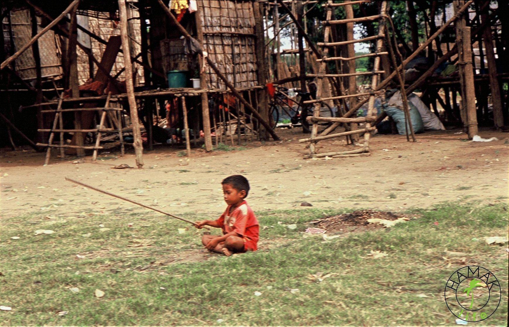 Chłopiec w wiosce na palach w Kambodży bawi się patykiem
