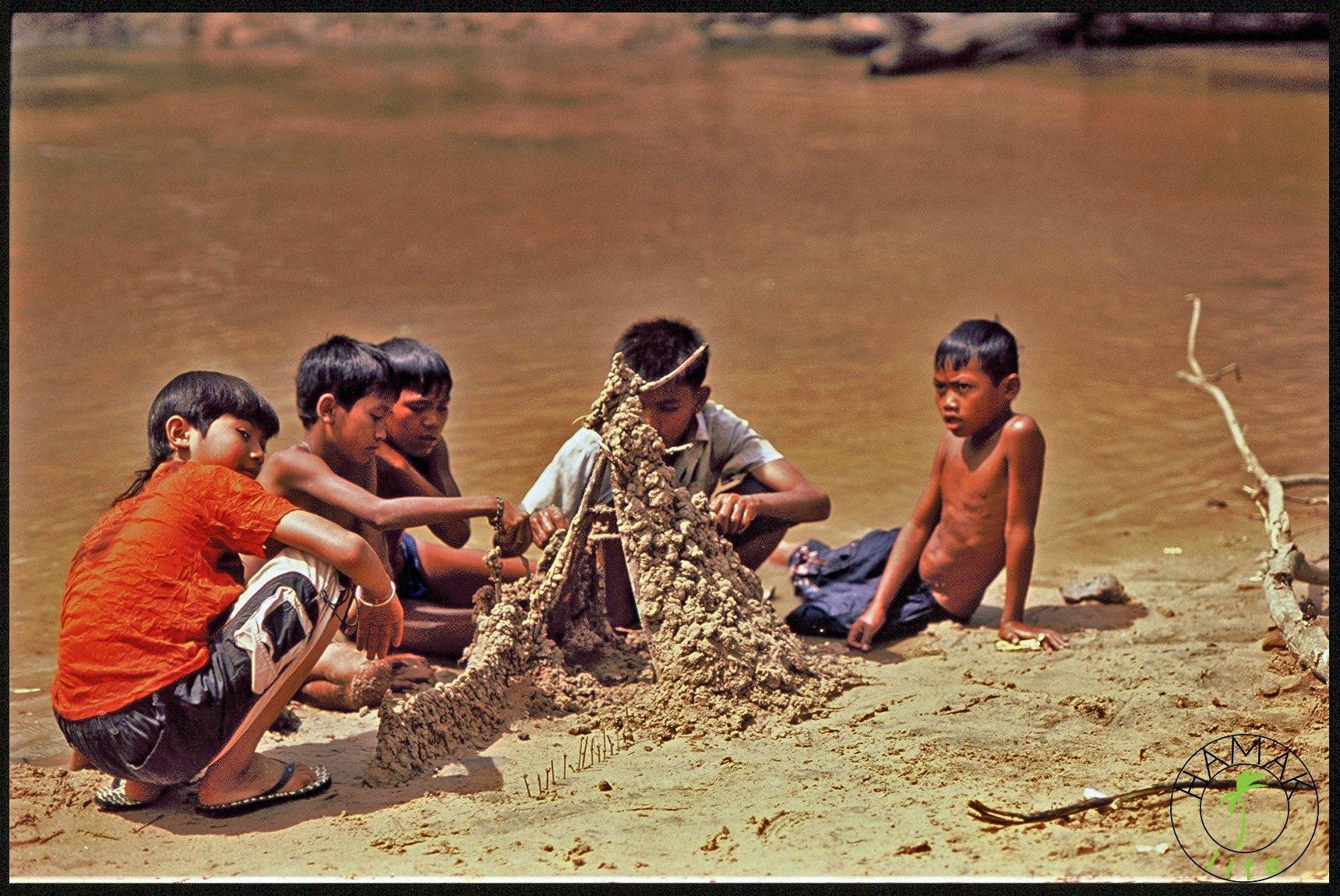 Chłopcy nad rzeką w Kambodży budują zamki z piasku