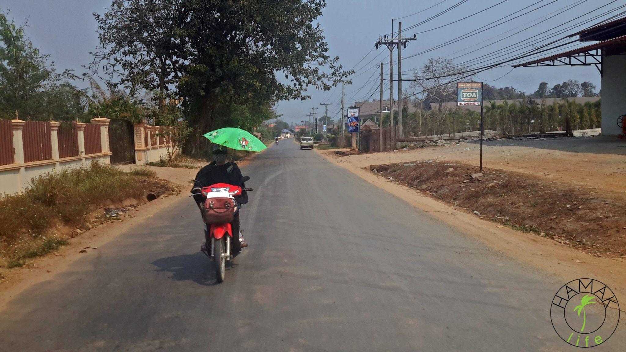 Houei Xai. Przy granicy Laosu z Tajlandią. Pani na skuterze z parasolką.