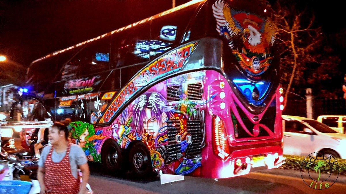 Ulica w Chiang Mai w nocy. Kolorowy autobus.
