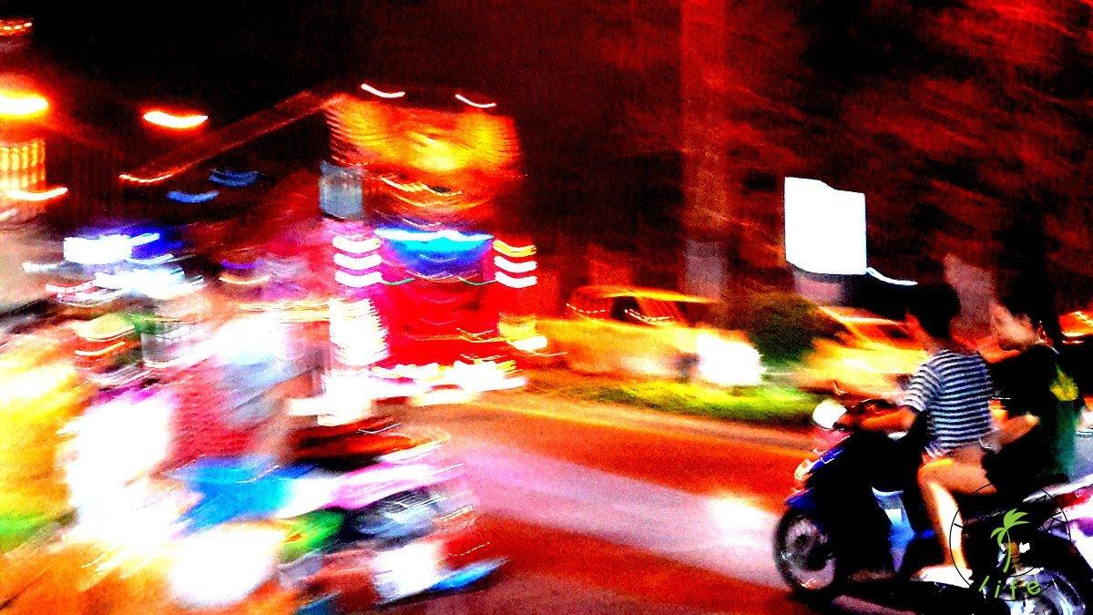 Ulica w Chiang Mai w nocy. Kolorowy autobus i skutery.