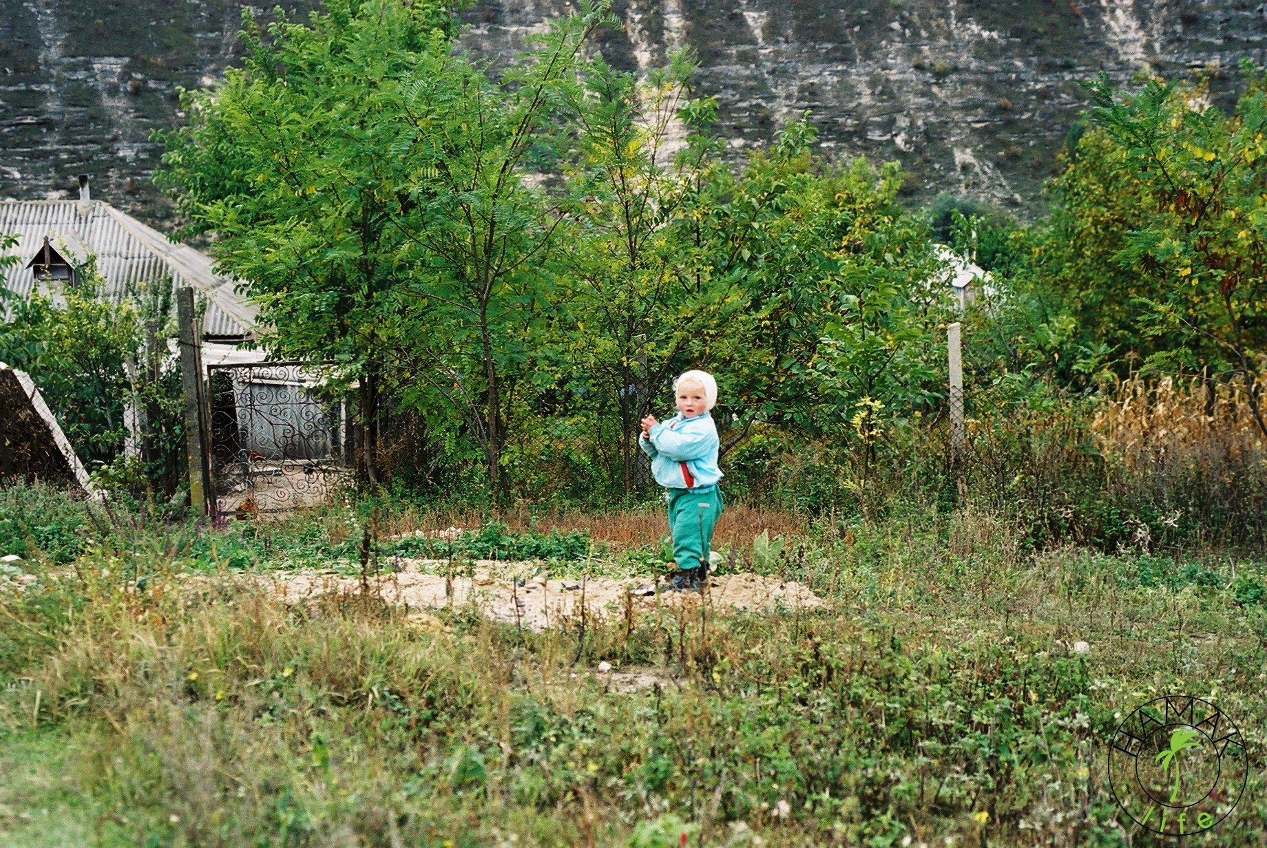 Wioska w Mołdawii. Dziecko obok chałupy.