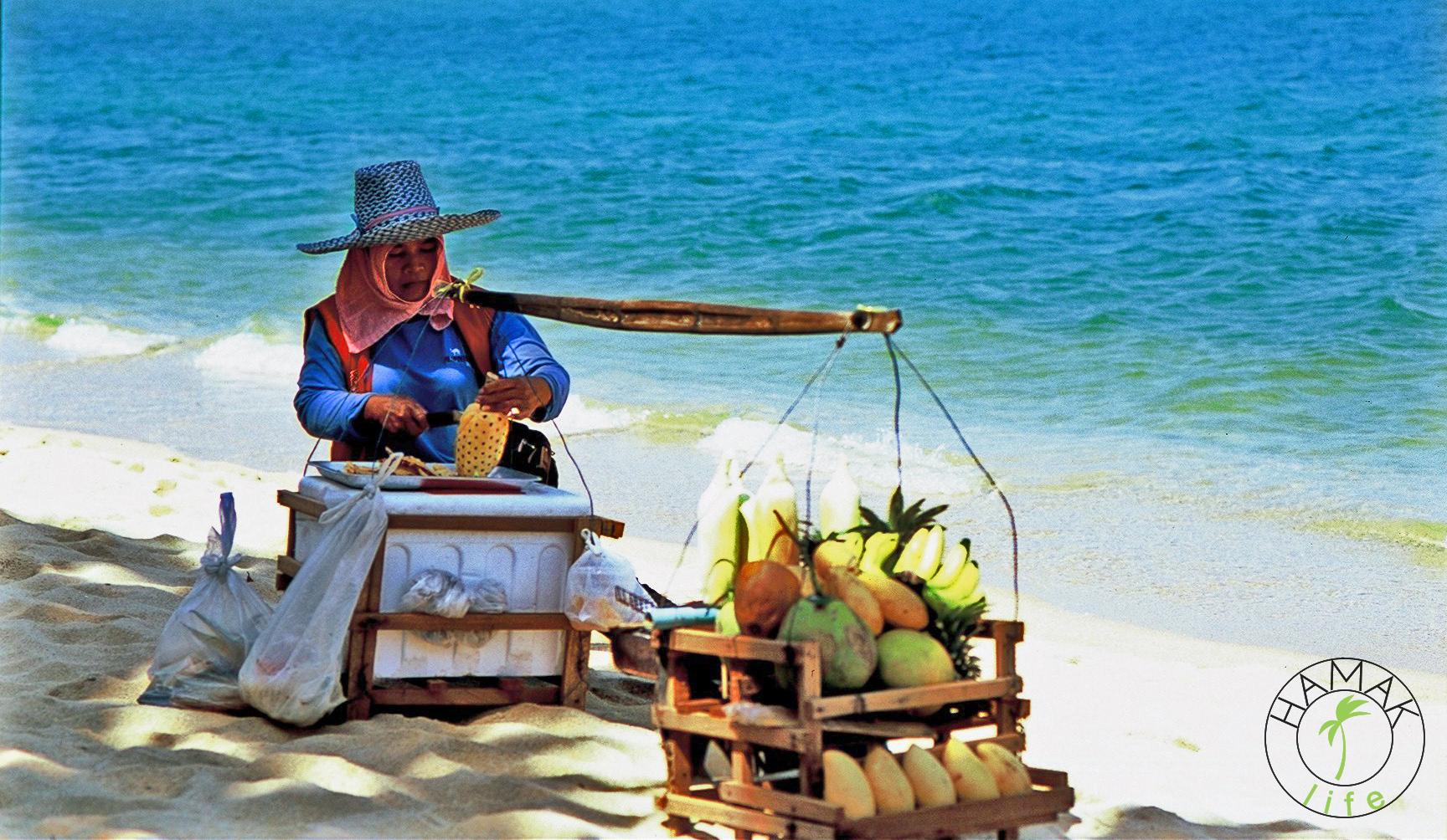 Plaża na Ko Samui. Lokalna kobieta sprzedaje owoce. Egzotyczne maski na użytek turystów.